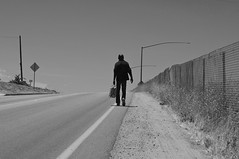 Drifter (blueteeth) Tags: highway road homeless walking chainlinkfence solitary alone loner outcast monochrome blackwhite street candid