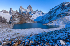 Fitz Roy and Snowy Landscape during twilight. (baddoguy) Tags: blue winter mountain lake snow reflection southamerica argentina horizontal iceage outdoors photography twilight nopeople glacier adventure clearsky alpenglow observationpoint eroded rockformation mountainrange chalten traveldestinations colorimage mtfitzroy famousplace beautyinnature nonurbanscene santacruzprovinceargentina rockobject