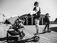 Street - We can't hold back progress (especially with wheels) (Franois Escriva) Tags: street blue light sea summer sky bw sun holiday black france beach colors children outdoors photo holidays noir candid streetphotography olympus nb rue whote blanc omd hoverboard