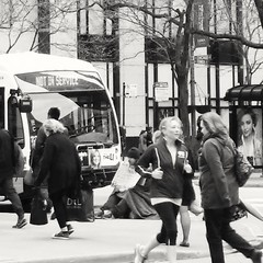 """Someone here has nowhere to go - a life """"not in service"""" (williamw60640) Tags: poverty blackandwhite woman chicago man bus sign cta streetphotography streetlife streetscene michiganave beggar busstop sidewalk blanket pedestrians rushhour treebranches jogger citybus homelessness homelessman chicagoave"""