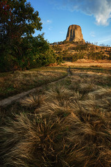 Rock Top (Brian Truono Photography) Tags: morning light red sky plants mountains nature colors grass rock stone clouds blackhills sunrise landscape volcano nationalpark rocks colorful butte natural nps erosion wyoming prairie geology nationalparkservice devilstower monolith hdr highdynamicrange nationalmonument igneousintrusion laccolith
