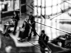 Re-Emergence - The Saga Continues (Anne Worner) Tags: people blackandwhite bw chicago geometric architecture lensbaby dark walking mono airport glow bokeh wheelchair curves escalator highcontrast olympus luggage ohare traveller f16 riding backpack underneath lightshow concourseb concoursebtoc em5 inthecrosshairs anneworner omdem5 velvet56 geometricsimpressionism