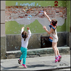 Bubble dance (Rob McC) Tags: street playing children fun happy jump outdoor poland krakow bubbles streetscene stretch