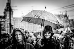 under an umbrella hides the rain (Gerrit-Jan Visser) Tags: bewerkt streetphotography amsterdam damrak central station umbrella rain hiding smile building people city urban hoody raincoat wet