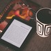 black E-book reader beside white and black mug - Credit to https://myfriendscoffee.com/