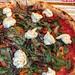 Nahaufnahme zwei Pizzen mit verschiedenen Zutaten auf Tischset in Zeitungs-Optik