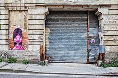 Mademoiselle Rose attend à la porte du garage (Isa-belle33) Tags: architecture urban urbain street streetphotography door porte garage boutique shop storefront magasin devanture fujifilm bordeaux old ancien abandoned möka graffiti streetart streetartbordeaux