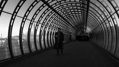 Tunes (Sean Batten) Tags: london england uk europe poplar poplarbridge dlr blackandwhite bw streetphotography street fuji x100f person candid city urban walking tunnel footbridge eastlondon docklands