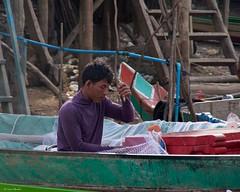 IMGP1433 Fixing fishing nets (Claudio e Lucia Images around the world) Tags: kompongphlukfloatingvillage siemreap cambodia kompong phluk floating village siem reap pluck cambogia people portrait man pentax pentaxart pentaxkp pentax18135 pentaxlens boat river water mud kampong fishing fisherman nets fishingnets