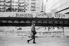 Fame is Overrated (ewitsoe) Tags: analog analogue bnw blackandwhite fm2 ilfordpan100 monochrome nikon warszawa erikwitsoe erikwitsoecom mono poland warsaw street woman walking sidewalk furcoat posters city urban gritty grain