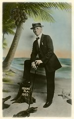 Man with Alligators and Coconut Tree, Miami, Florida, 1922 (Alan Mays) Tags: ephemera postcards realphotopostcards rppc photos photographs souvenirphotos souvenirs portraits foundphotos backdrops studioprops men ties bowties suits hats canes eyeglasses glasses spectacles clothing clothes alligators starfish animals beaches shores seashores oceans water trees palmtrees coconuttrees coconuts stumps treestumps tinted handtinted handcolored handpainted humor humorous funny comic amusing strange fake danger dangerous miami fl florida flor 1922 1920s antique old vintage