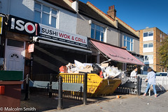 A New Shop In The Making (M C Smith) Tags: new skip work waste rubbish shutters door man woman sign fencing walls fence white pentax k3 letters numbers black symbols bollards chain flats shops awning shadows blue blockpaving yellow sky green trees car parking