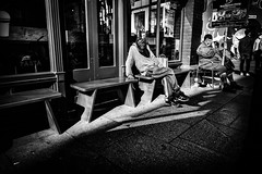 Reasons (Kieron Ellis) Tags: man men people sitting tired bench window cafe shadow reflection bright light sign hat bottle bag pavement candid street blackandwhite blackwhite