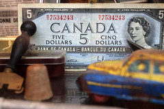 Still Life with Old Money (♫ marc_l'esperance) Tags: luminous canadian money currency tin toy depthoffield 35mm carlzeissjena stilllife luxmatic marclesperancephoto allrightsreserved 2019 montreal canada vintage objects manualfocus manualexposure queenelizabethii 3d flektogon fuji xe2 apsc 5dollars 5dollarbill bankofcanada ddr macro