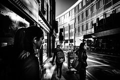 Directions (Kieron Ellis) Tags: woman women people walking directions bright light shadow bag headphones sign candid street urban windows glass blackandwhite blackwhite monochrome