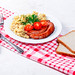 Delicious porridge with sausages and bread with dish towel on white wooden background