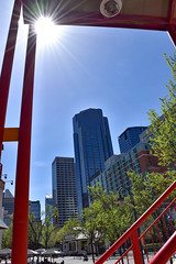 Downtown Calgary Skyline (darletts56) Tags: sky blue sun sunshine ray rays building buildings tree trees green red white street downtown stairs railing post posts light lights lamp lamps vehicle people seat seating umbrella umbrellas reflection