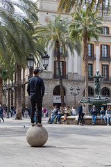 Man balancing on a stone ball under palm trees, next to  fountain of the Three Graces and helmet lamps designed by Antoni Gaudi in Barcelona, Spain (verchmarco) Tags: spain barcelona spanien provinzbarcelona es people menschen city stadt street strase group gruppe tourism tourismus travel reise building gebäude daylight tageslicht road tourist architecture diearchitektur adult erwachsene urban städtisch outdoors drausen pavement pflaster many viele vacation urlaub woman frau man mann town dorf path dawn macromondays fence interior eos day truck historic