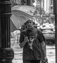 Chicago in the rain..... (Kevin Povenz Thanks for all the views and comments) Tags: 2018 july kevinpovenz illinios chicago windycity street streetphotography streetportrait portrait blackandwhite bw canon7dmarkii sigma24105art man rain umbrella headphones walking city downtown male