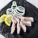 Pieces of salted herring with onion rings and lemon slices on a black stone tray
