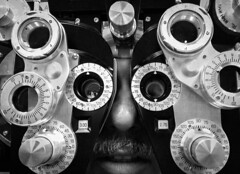 I See You (Greg Adams Photography) Tags: optician eyeexam me machine lenses device exam repetition multiple many adjustment hhsc2000 indoor blackandwhite colorblind bw nose face mustache gregadams selfportrait