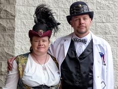 Steampunk Couple (J Wells S) Tags: steampunkcouple portrait candidportrait beard costumes dressup bowlerhat bowtie feathers steampunksymposium hat eastgate cincinnati ohio cosplay holidayinneastgate