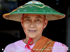 2013-10a Asian Conical Hat 2019 (01) (Matt Hahnewald) Tags: matthahnewaldphotography facingtheworld people character head face eyes expression shaved pink robe clothing green hat sunhat respect dignity dedication commitment religion religious traditional cultural holy buddhist buddhism nun shavedhead roadside loikow kayahstate myanmar burma asia asian burmese female mature woman women nikond610 nikkorafs85mmf18g 85mm resized 1200x900pixels horizontal street portrait closeup headshot fullfaceview outdoor colour posing authentic clarity smiling smile conceptual 4x3ratio consensual conical lookingcamera ricepaddyhat middleaged