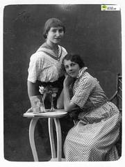 tm_6181 (Tidaholms Museum) Tags: svartvit positiv gruppfoto människor dekor rekvisita möbel bord blomvas