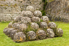 Stone balls in Pevensey Castle (Keith in Exeter) Tags: pile ammunition shot ball catapult stone pevensey castle sussex ancient ruins english heritage grass stonework wall