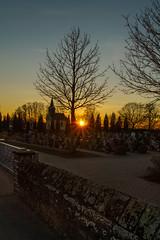 Am Friedhof geht die Sonne unter (KaAuenwasser) Tags: sonnenuntergang sonne strahlen sonnenstern landschaft ort dorf platz friedhof kapelle kirche grabsteine grabstein stein mauer ruhe abend himmel farben farbe bunt weg wege strase baum bäume pflanzen gebäude bauwerk tor