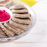 Boiled tongue with horseradish sauce on white wooden table thumbnail