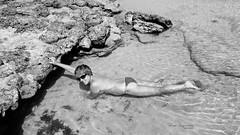 Trapped in a lagoon (piotr_szymanek) Tags: fuerteventura marzka woman milf outdoor nude blackandwhite water sea ocean beach stone lava sand naturist topless nobra glasses sunglasses lagoon rock 1k 5k 20f 10k 20k 30k