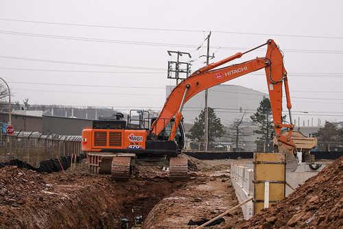 Our Hitachi 470LC straddling this trench in Burlington, Ontario. Updates of the project were featured in a recent blog post.