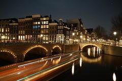 Night in Amsterdam (Kathy~) Tags: winter amsterdam holland netherlands night lighttrails boatlights lights artificial bridge city fc perpetualchallenge
