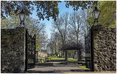 Through the Gates in Springtime (clive_metcalfe) Tags: christchurch dorset uk priory gardens springtime trees lamps seat bench grass sky wall stone path gate open