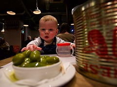 Oh!  What's that?! (matthewblackwood10) Tags: baby food olives want reach grab hungry kid kids babies boy green olive restaurant indoors light lights tin aluminium happy cup bowl
