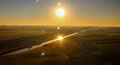 Schiphol Sunrise (Andy.Gocher) Tags: schiphol andygocher canon100d sigma18250 europe holland netherlands landscape sunset sun reflection water lens flare land horizon