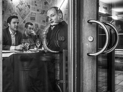 three pairs of eyes (judydeanclasen) Tags: cafe bar düsseldorf newspaper drinkingglasses eyecontact men streetphotography mono window