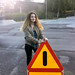 Girl Holding Road Sign at a Skate Park
