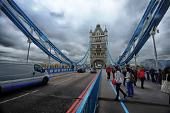 Crossing Tower Bridge in London, United Kingdom (` Toshio ') Tags: toshio london england unitedkingdom bridge towerbridge europe tower people road street thames river thamesiver tourists fujixe2 xe2 man woman cityhall van car traffic clouds storm
