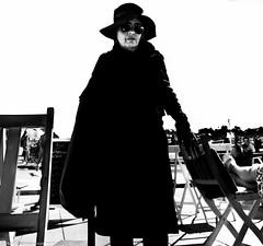 Dark and dangerous. (Neil. Moralee) Tags: neilmoralee neilmoraleenikond7100 woman girl lady mature dark black white bw bandw mono monochrome blackandwhite ring finger hat silhouete chairs dangerous porto portugal neil moralee nikon d7100 candid street witch modern contrast noir film art artistic push process lightroom sinister hard light