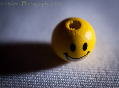 Happiness In The Hard Light (HMM) (13skies) Tags: hardlightphotography hard yellow happyface macro macroscopic sonyalpha100 flashlight light sidelight closer bead small a100 happymacromondays hmm happymacromonday cloth macromondays