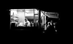 Guten Appetit (Mister G.C.) Tags: blackandwhite bw sonya6000 sonyalpha6000 mirrorless streetphotography urbanphotography candid street monochrome photograph image people night nighttime nightphotography framed framing food foodtruck foodstand snackbar dark unposed urban town city sony a6000 f28 28mm primelens soligor soligorfd wide wideangle vintagelens legacyglass manualfocus manualfocusing emountadadpter schwarzweiss strassenfotografie walsrode niedersachsen lowersaxony germany deutschland europe