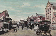 Russell Street, Toowoomba, Qld - circa 1910 (Aussie~mobs) Tags: russellstreet toowoomba queensland vintage australia colouredshellseries streetscape buggy sulky shops stores buildings boys bicycle hotelnational