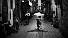 (Salmonpink) Tags: street villageincity flying bike kite readingonbike lightandshadow night