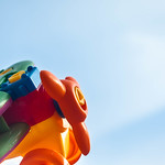 Closeup view of plastic toy plane against clear blue sky thumbnail