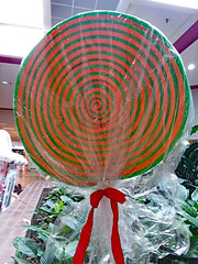 Giant Wrapped Lollipop. (dccradio) Tags: lumberton nc northcarolina robesoncounty indoor indoors inside saturday winter december saturdayafternoon goodafternoon afternoon samsung galaxy smj727v j7v cellphone cellphonepicture mall shoppingmall biggsparkmall shoppingcenter christmas holiday christmasdisplay holidaydisplay candy lollipop sucker redribbon giant largerthanlife greenery green orange