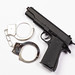 Gun and handcuffs on white background