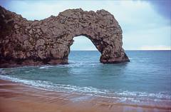 arching (Ron Layters) Tags: limestone arch jurassiccoast naturalarch hole rocks waves portlandlimestone geology folds beach seaside coast sea horizon covelulworth dorset england unitedkingdom slidefilmthenscanned slide transparency fujichrome velvia leica r6 leicar6 ronlayters