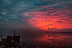 Surprise! (langdon10) Tags: canada laurentiadesgagnes quebec stlawrenceriver sunset water calm clouds ice ship tanker winter